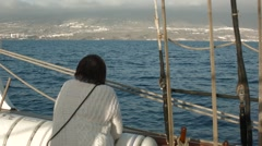 Lone passenger looks out to sea from the deck of a tall ship - stock footage