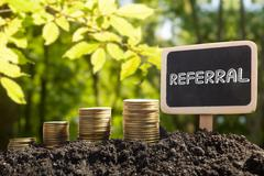 Referral - Financial opportunity concept. Golden coins in soil Chalkboard on Stock Photos