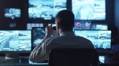 Security officer is drinking coffee while working on a computer in a dark office - stock footage