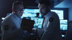 Security officer is using a tablet computer in a dark monitoring room - stock footage