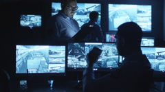 Security officer is using a tablet computer in a dark monitoring room Stock Footage