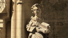 Child holding a book statue on the facade of Stephansdom, Vienna Stock Footage