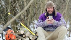 Bearded man drinking tea in the forest. Bearded woodcutter at rest in winter. - stock footage