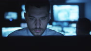 Stressed and tired security officer is working on a computer in a dark office - stock footage