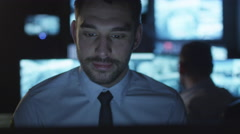 Focused security officer is working on a computer in a dark monitoring room - stock footage