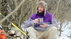 Bearded man drinking tea in the forest. Bearded woodcutter at rest in winter. Stock Footage
