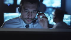 Technical support specialist is talking on a headset while working on computer - stock footage