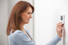 Woman Adjusting Digital Central Heating Thermostat Control Stock Photos