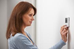 Woman Adjusting Thermostat On Central Heating Stock Photos