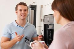 Engineer Giving Advice To Woman On Kitchen Repair - stock photo