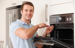 Engineer Reapiring Domestic Oven In Kitchen Stock Photos
