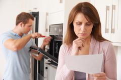 Woman Looking Concerned At Bill For Repair Of Kitchen Appliance - stock photo