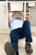 Plumber Working Under Sink With Wrench Stock Photos