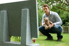 Father Placing Teddy Bear On Child's Grave In Cemetery Kuvituskuvat