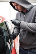 Car Thief Using Crowbar To Open Door Stock Photos