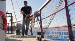 Crew member tidying up ropes on a tall ship in the Canary islands - stock footage