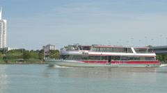 Tourist boat floating on Danube river, near Donau City, Vienna Stock Footage