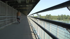 Riding a bike on a bridge over Donau river, Vienna Stock Footage