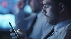 Security officer is checking social media on smartphone while working in office - stock footage