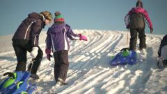 three girls and mother with bobsleds in snow - stock footage