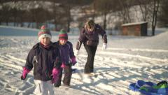 mother with little daughters and sleds in snow - stock footage