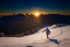 Ascending to the top. Ski mountaineering Cross country skiing alone uphill in Stock Photos