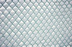 Snow-covered fence, metal mesh Stock Photos