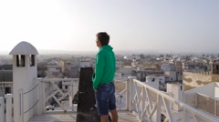 Man stands on top in medina and looking on sky, morocco, essaouira Stock Footage
