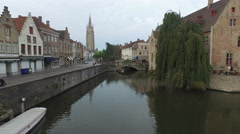 People on the street, tower of Church of Our Lady and Groenerei Canal in Bruges Stock Footage