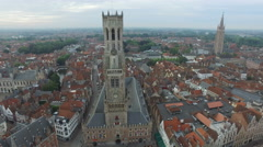 Aerial shot of Belfry of Bruge, Church of Our Lady and buildings in Bruges Stock Footage