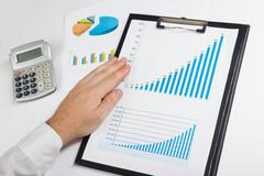 Businessman counting losses and profit working with statistics, analyzing Stock Photos
