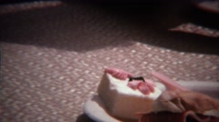 1973: Manly men eating dainty little cakes at summer family reunion. Stock Footage