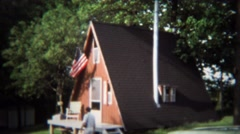 1973: Mountain A-frame construction style house with USA flag. - stock footage