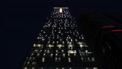 Look up to illuminated checkered tower facade at night. Lights turn on and off Stock Footage