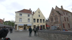 People walking in Vismarkt near Brasserie Mozarthuys in Bruges Stock Footage
