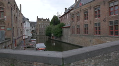 View of moored boats and a swan swimming on Canal Dijver in Bruges Stock Footage