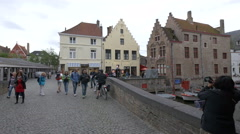 People walking in Vismarkt and Canal Boat Ride near Dijver Canal in Bruges Stock Footage