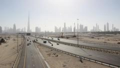 Deserted Dubai roads time lapse, Burj Khalifa far in dusk, city towers in line Stock Footage