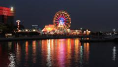 Colorful lights and Ferris wheel reflection in water surface, time lapse Stock Footage