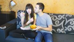 Young Couple Watching TV on the Sofa in the Living Room end eating chips Stock Footage