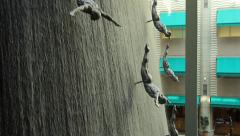 Waterfall at Dubai Mall, man figures against falling water streams Stock Footage