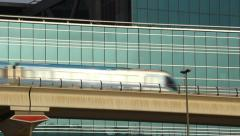 Dubai metro train move on elevated railway against glass facade Stock Footage