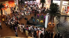 Small stage in large mall hall, girls dance, visitors stand around and look Stock Footage