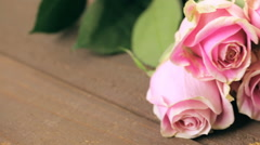Assorted chocolates with pink roses on wood table. Stock Footage