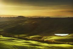 Stock Photo of Tuscany, rural landscape on sunset, Italy. Lake and green fields