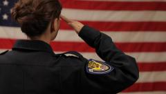 Female Police Officer Saluting Flag Stock Footage
