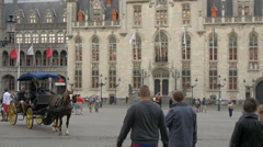 View of horse carriages and people in front of Provinciaal Hof in Markt, Bruges Stock Footage