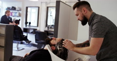 Shot of a young man having his hair washed at a hair salon. Shot on RED Epic. Stock Footage