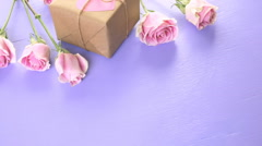Gift box wrapped in recycled paper and decorated with pink heart with pink roses - stock footage