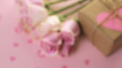 Gift box wrapped in recycled paper and decorated with pink heart with pink roses Stock Footage
